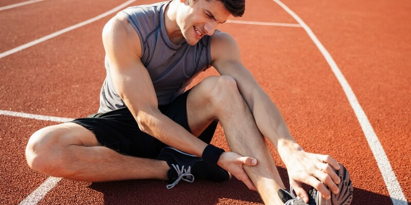 man grasping foot in hunched position at a running track