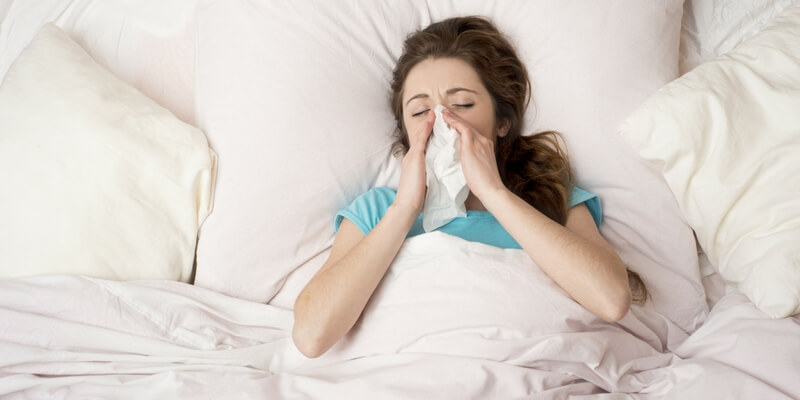 women with allergies in blue shirt laying in white bed blowing nose