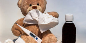 teddybear holding thermometer and tissues