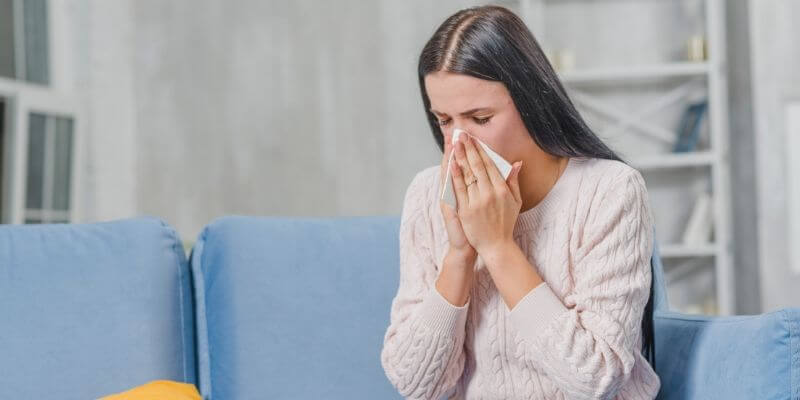 girl sneezing due to summer allergies